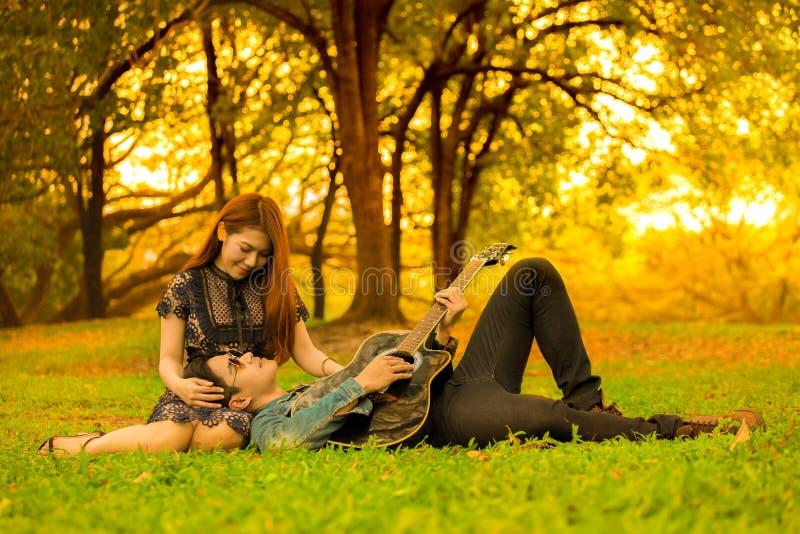 os pares novos asiáticos no amor apreciam o homem que joga a guitarra que encontra-se nos pés da amiga no parque do outono do jar fotografia de stock royalty free