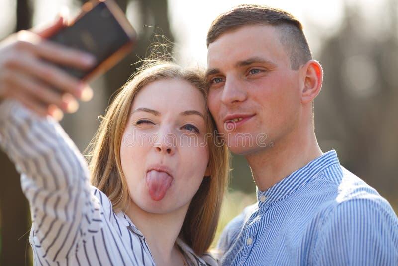 Os pares novos bonitos fazem as caras e tomam o selfie fora Juventude, com referência a fotos de stock royalty free