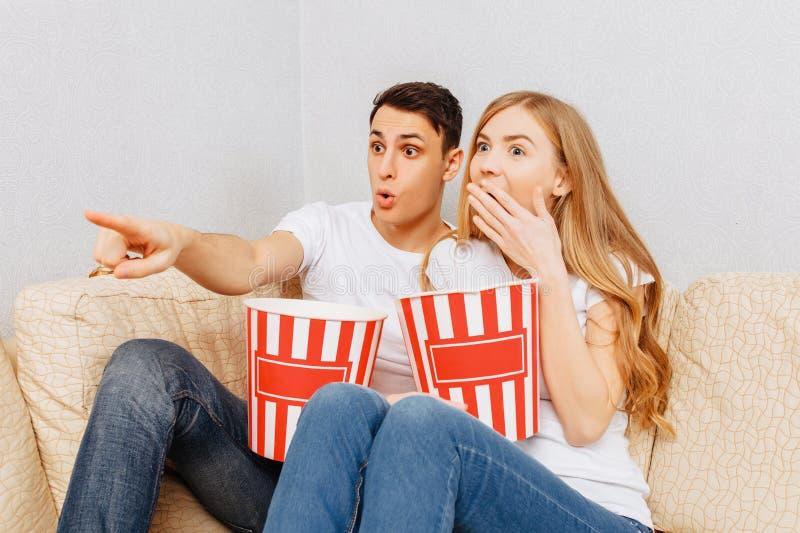 Os pares novos bonitos, homem e mulher, olham filmes e para comer a pipoca, sentando-se em casa no sofá fotos de stock