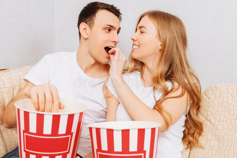 Os pares novos bonitos, homem e mulher, olham filmes e para comer a pipoca, sentando-se em casa no sofá imagens de stock