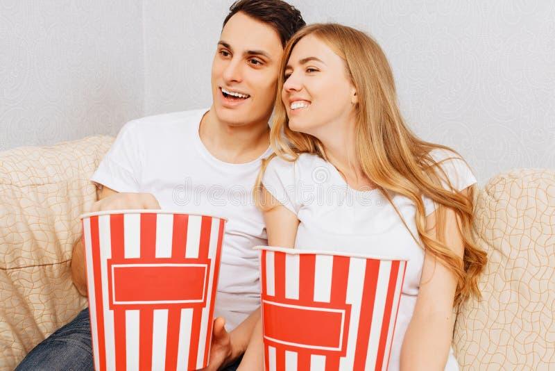 Os pares novos bonitos, homem e mulher, olham filmes e para comer a pipoca, sentando-se em casa no sofá fotos de stock royalty free