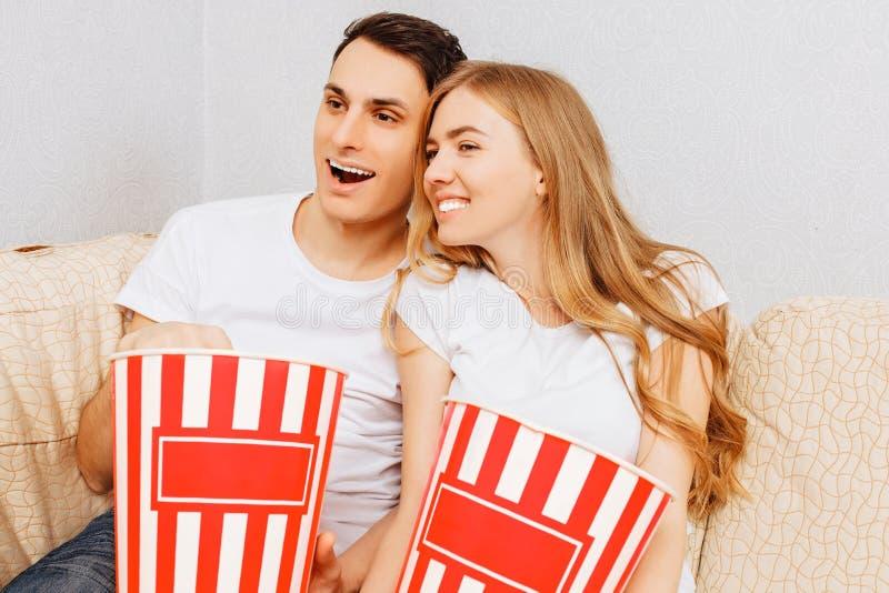 Os pares novos bonitos, homem e mulher, olham filmes e para comer a pipoca, sentando-se em casa no sofá imagem de stock royalty free