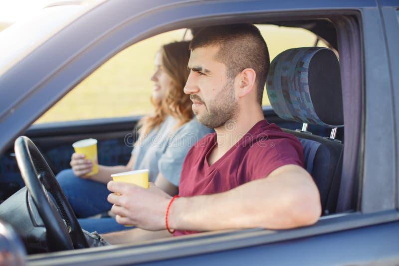 Os pares novos com café para dentro do carro, têm o resto que monta ao longo da estrada, família feliz para passar junto o tempo, imagens de stock