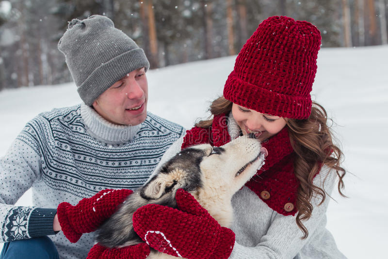 Os pares novos com um cão ronco que anda no inverno estacionam, homem e mulher que abraçam um cão foto de stock