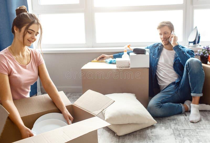 Os pares novos da família compraram ou alugaram seu primeiro apartamento pequeno Mulher que desembala o material Guy Talk no tele foto de stock