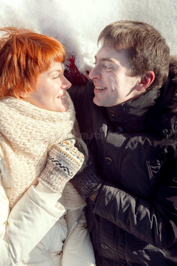 Os pares novos de sorriso felizes abraçam na neve e na vista entre si fotos de stock