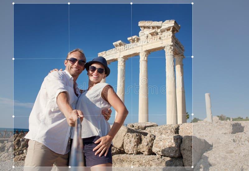 Os pares novos de sorriso tomam uma foto do selfie em ru?nas antigas foto de stock royalty free