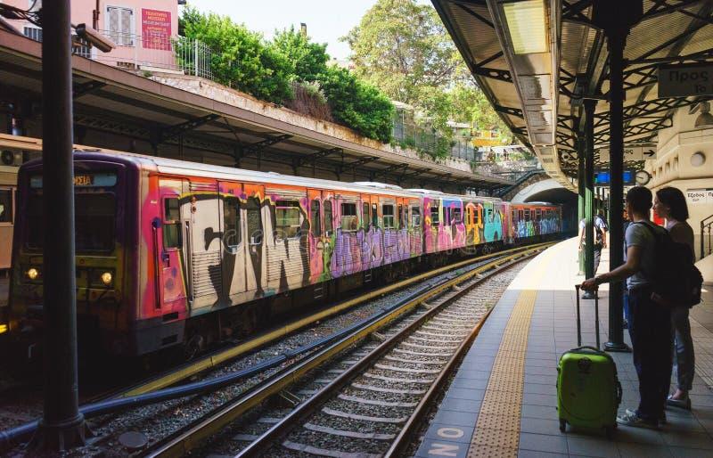 Os pares novos de viajantes com uma bagagem da mala de viagem e de mão esperam a chegada do metro fotos de stock