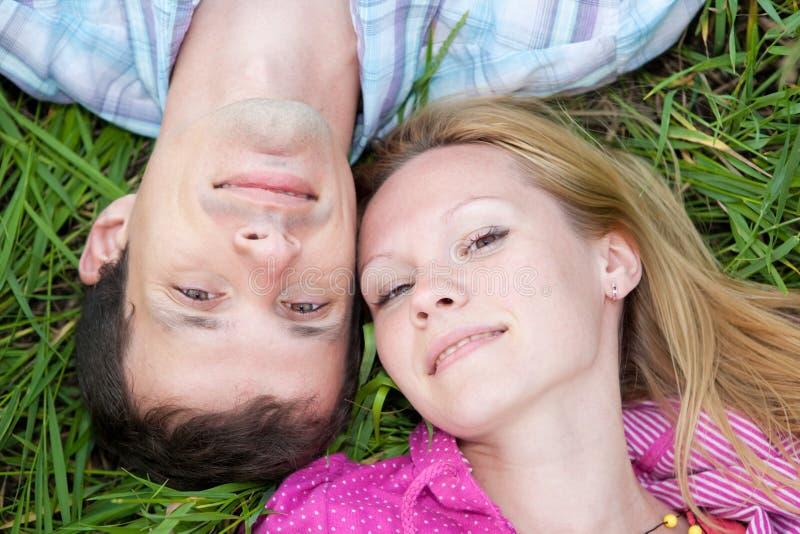 Os pares novos do amor colocam na grama verde ao ar livre. fotografia de stock royalty free