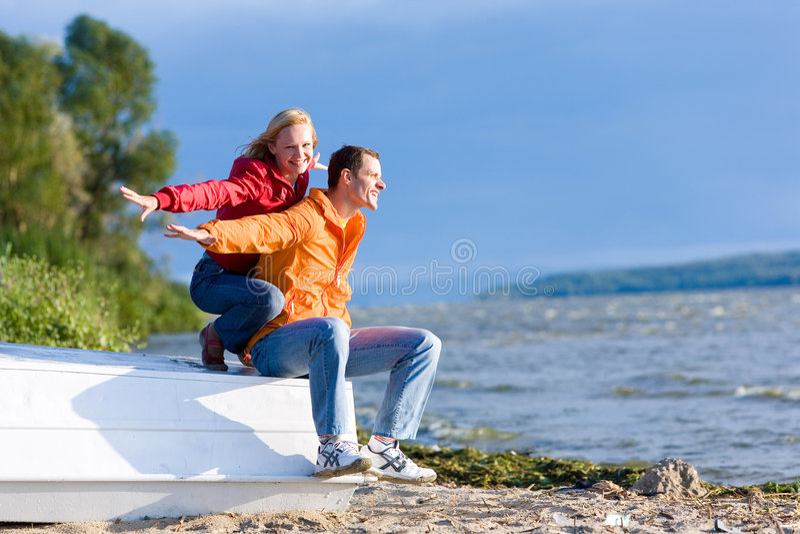 Os pares novos do amor sentam-se no barco na costa do rio fotos de stock royalty free