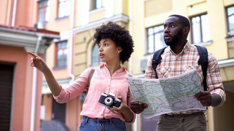 Os pares novos do turista com a câmera do mapa e da foto, escolhendo o sentido, viajam fotos de stock royalty free