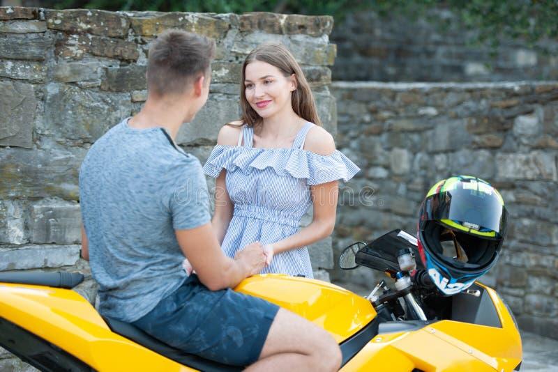Os pares novos em um motor bike em uma tarde do fim do verão imagens de stock royalty free