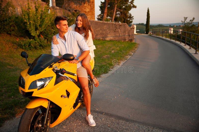 Os pares novos em um motor bike em uma tarde do fim do verão imagem de stock