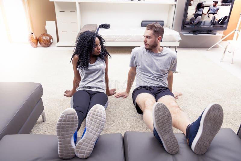 Os pares novos estão treinando fazendo a ginástica em casa foto de stock