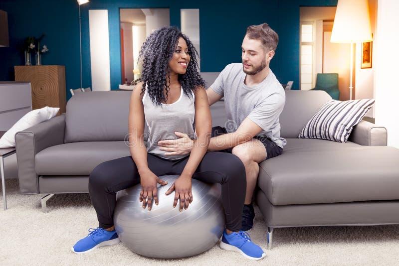 Os pares novos estão treinando fazendo a ginástica em casa fotografia de stock royalty free