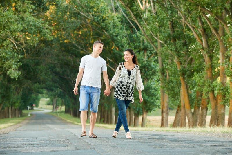 Os pares novos felizes andam na estrada secundária exterior, conceito romântico dos povos, temporada de verão foto de stock