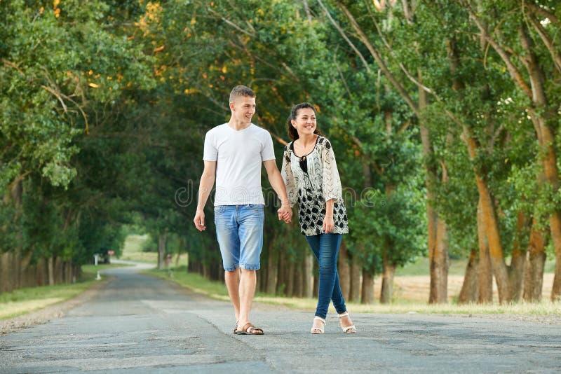 Os pares novos felizes andam na estrada secundária exterior, conceito romântico dos povos, temporada de verão fotografia de stock