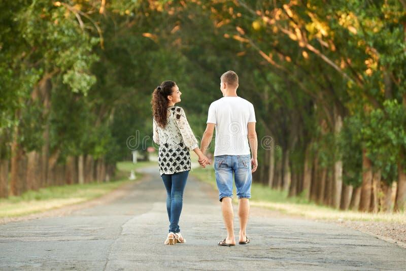 Os pares novos felizes andam na estrada secundária exterior, conceito romântico dos povos, temporada de verão fotografia de stock royalty free