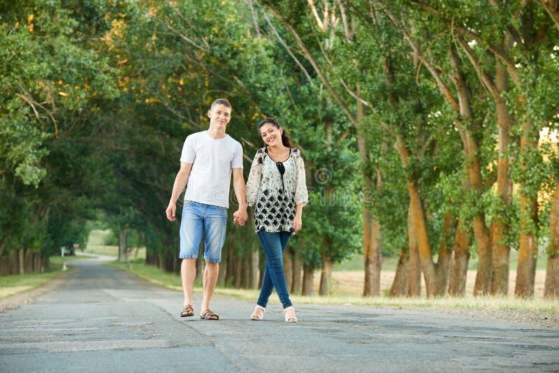 Os pares novos felizes andam na estrada secundária exterior, conceito romântico dos povos, temporada de verão imagem de stock