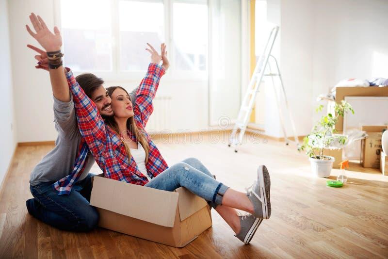 Os pares novos felizes apenas moveram a casa nova que desembala caixas; tendo o divertimento imagens de stock royalty free