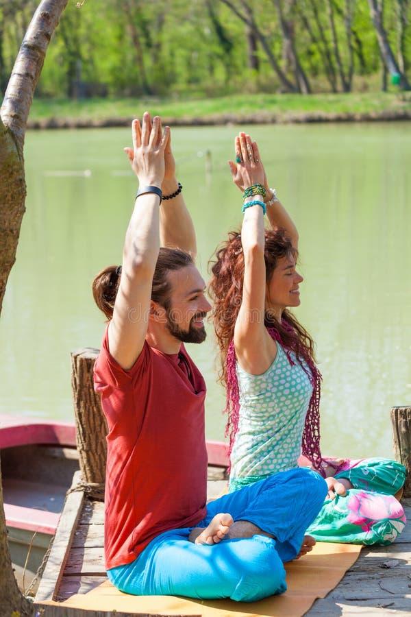 Os pares novos felizes apreciam fazer a ioga no dia de verão ensolarado do lago imagem de stock royalty free