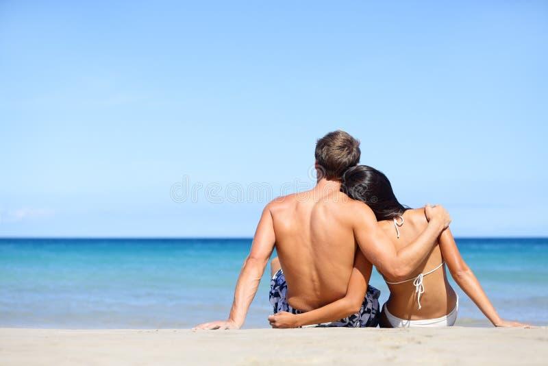 Os pares novos felizes na praia de relaxamento do amor vacation imagens de stock