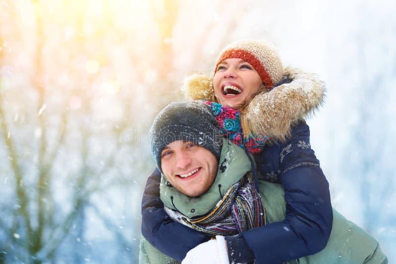 Os pares novos felizes no inverno estacionam o riso e ter do divertimento Família ao ar livre fotografia de stock royalty free