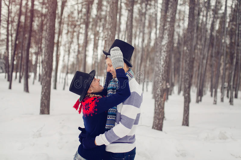 Os pares novos felizes no inverno estacionam ter o divertimento Família vestida nos cilindros engraçados dos chapéus imagem de stock royalty free