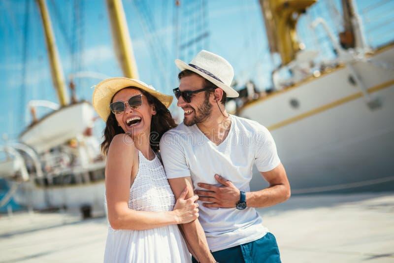 Os pares novos felizes que andam pelo porto de um mar turístico recorrem foto de stock royalty free