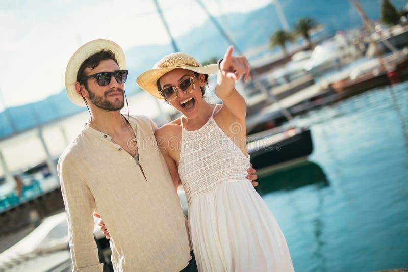Os pares novos felizes que andam pelo porto de um mar turístico recorrem imagens de stock