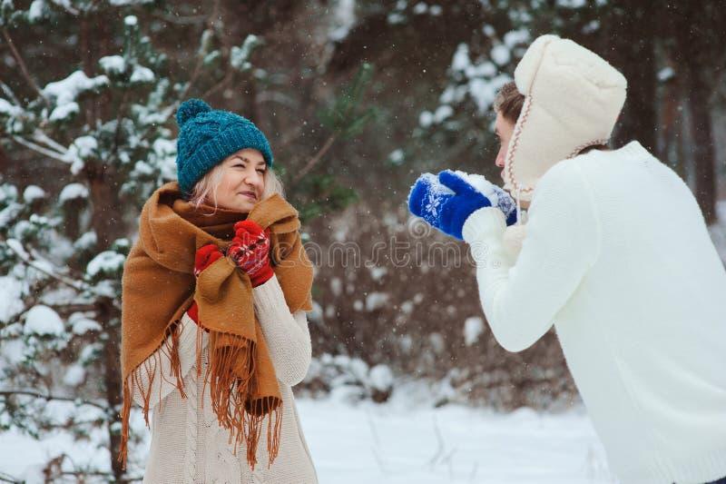 os pares novos felizes que jogam no inverno andam, jogando bolas de neve e tendo o divertimento exterior fotografia de stock royalty free