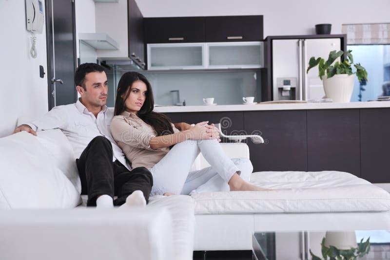 Os pares novos felizes relaxam em casa fotos de stock royalty free