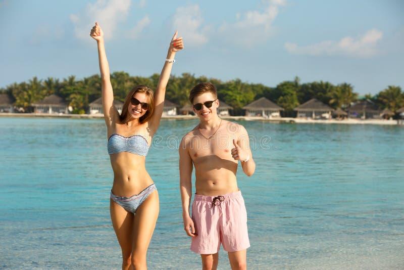 Os pares novos felizes têm o divertimento e relaxam na praia O homem e a mulher mostram os polegares que apreciam acima férias pe imagem de stock