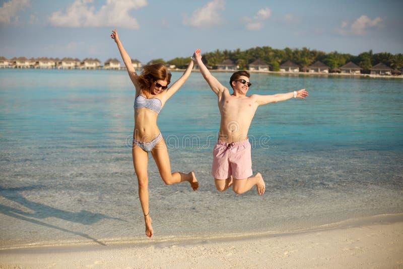 Os pares novos felizes têm o divertimento e relaxam na praia O homem e a mulher saltam guardando as mãos e o sorriso Bungalows do fotos de stock royalty free