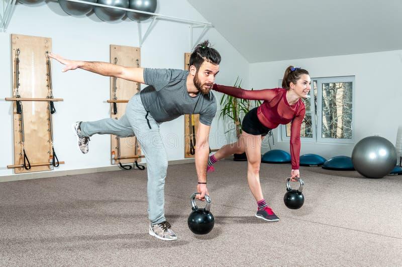 Os pares novos malham o exercício no gym, foco seletivo da aptidão do kettlebell imagens de stock royalty free