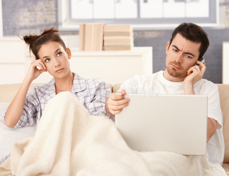 Os pares novos na cama equipam a mulher de funcionamento furada foto de stock