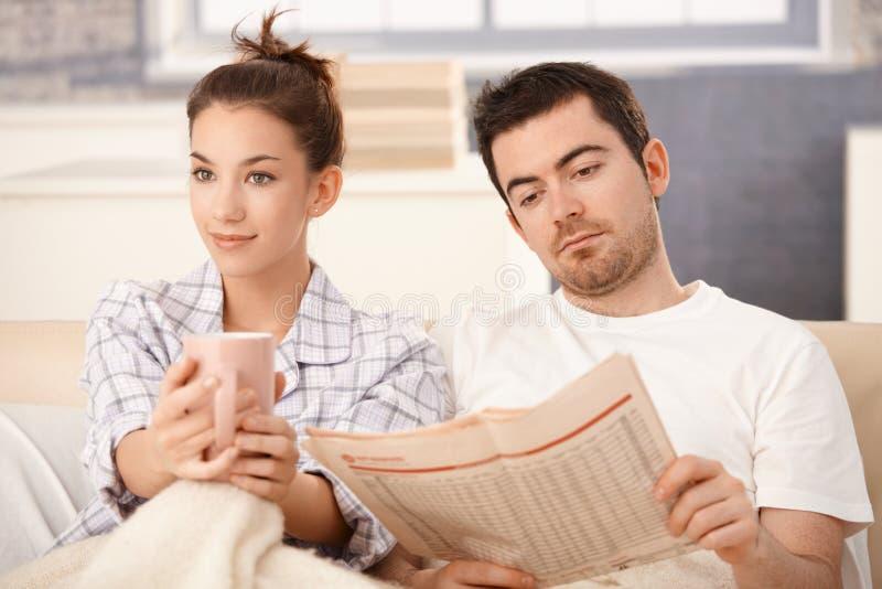 Os pares novos na cama equipam o chá bebendo da mulher da leitura imagens de stock royalty free