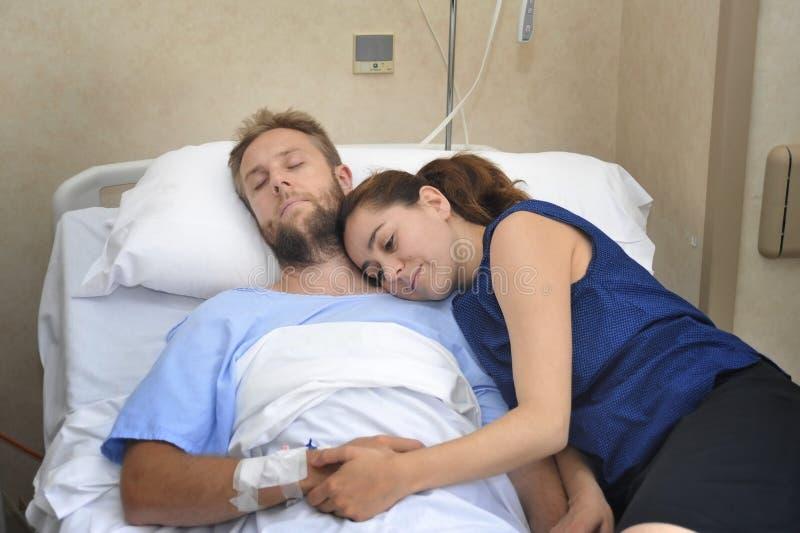 Os pares novos na sala de hospital equipam o encontro na mulher preocupada cama que guarda seu inquietação da mão imagens de stock