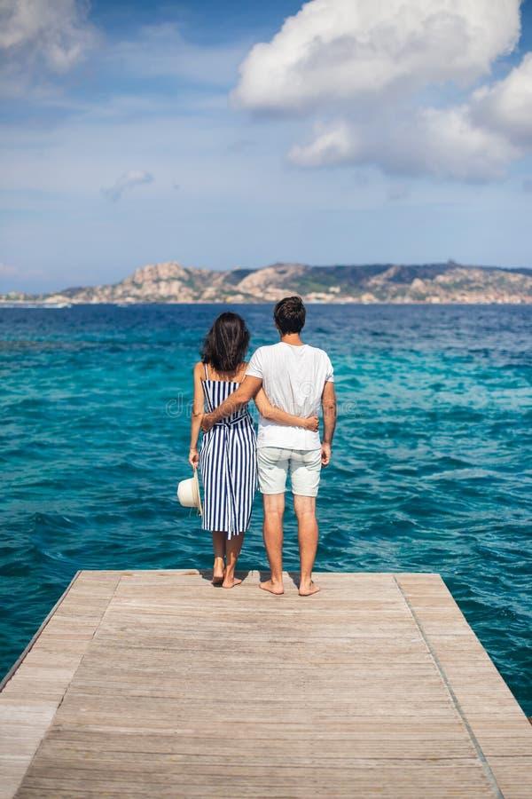 Os pares novos no amor apreciam a paisagem bonita do mar no cais nele imagens de stock royalty free