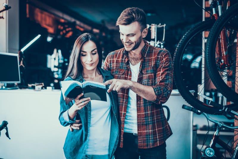 Os pares novos olham o catálogo escolhem a bicicleta nova imagem de stock royalty free
