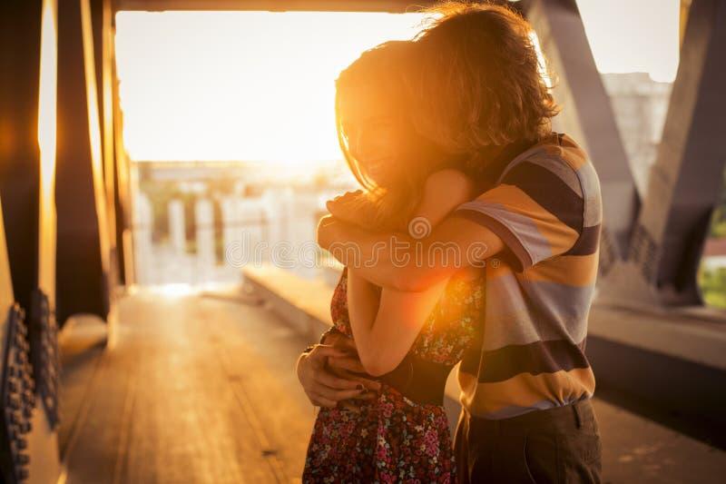 Os pares novos que abraçam nos alargamentos do por do sol iluminam-se em uma ponte c foto de stock