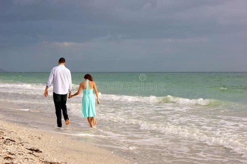 Os pares novos que andam ao longo do bonita encalham como pores do sol fotos de stock royalty free