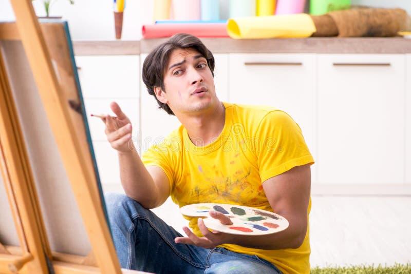 Os pares novos que apreciam a pintura em casa imagens de stock