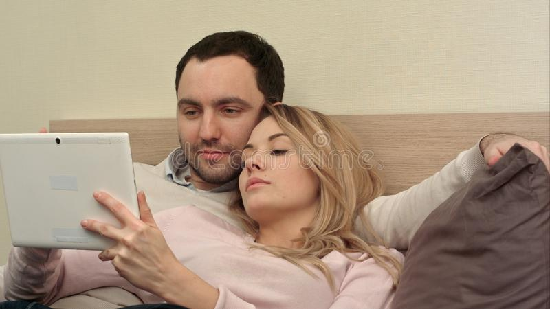 Os pares novos que encontram-se na cama fazem a compra sobre o Internet usando a tabuleta usando o tablet pc fotos de stock