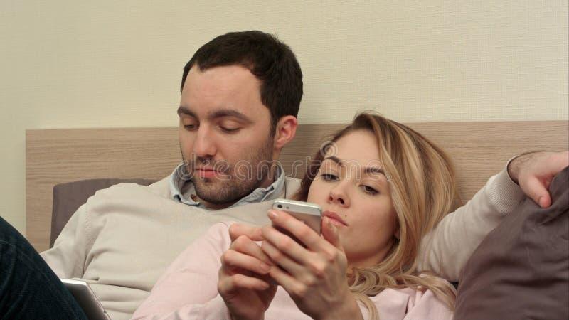 Os pares novos que encontram-se na cama, homem que usa a tabuleta digital, furaram a mulher que usa o smartphone fotos de stock royalty free
