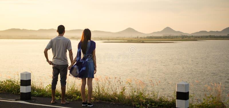 Os pares novos que guardam a mão e consideram a paisagem bonita foto de stock