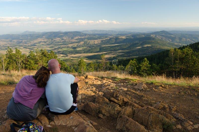 Os pares novos que sentam-se na montanha cobrem no verão fotografia de stock