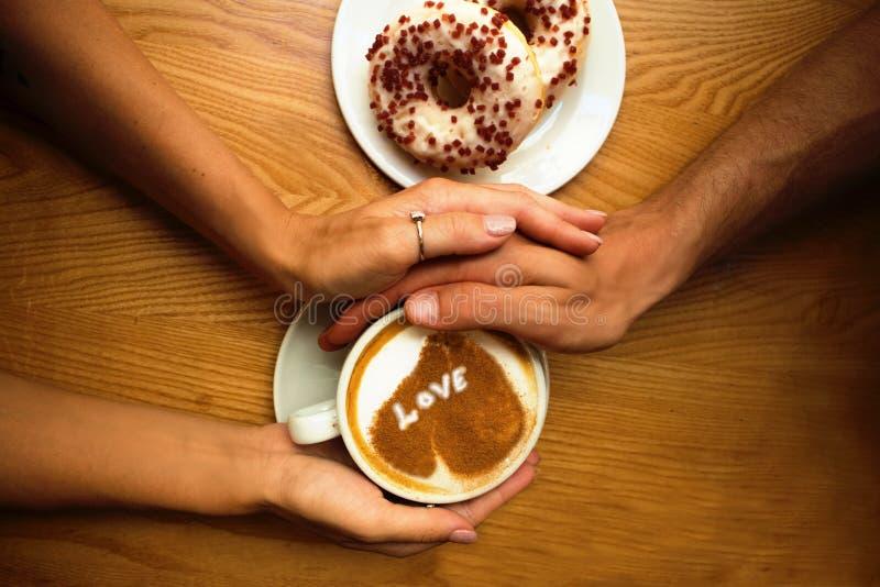 Os pares novos românticos sentam-se no café, mãos do close up que guardam uma xícara de café com coração neles e 2 anéis de espum imagem de stock