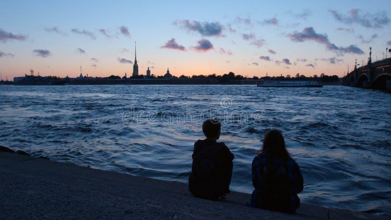 Os pares novos sentam-se em uma terraplenagem do rio de Neva no backgro de Peter e de Paul Fortress fotos de stock