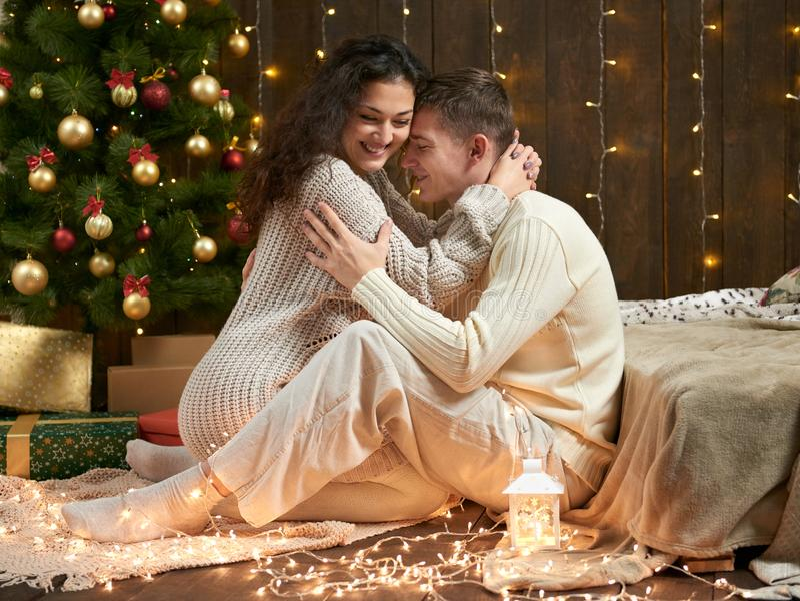 Os pares novos sentam-se no assoalho no interior de madeira escuro com luzes Noite e conceito românticos do amor Feriado do ano n fotos de stock